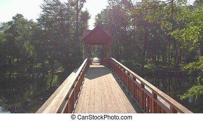 Wooden bridge in the forest old pedestrian empty green trees sun glare river forward push in camera movement