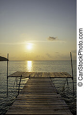 Wooden bridge in the sea and Golden reflections of the Sun