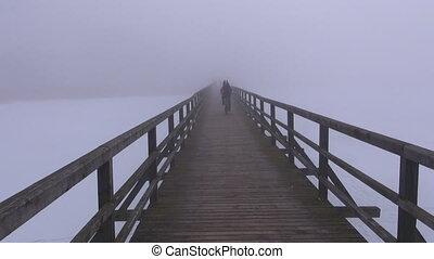 wooden bridge in winter mist fog