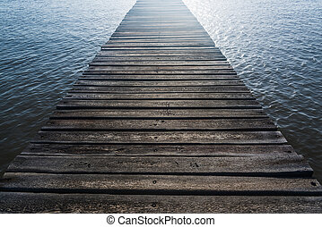 wooden bridge juts out into of the sea - wooden batten...