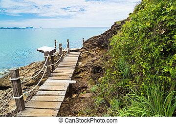 Wooden bridge on island with blue sky