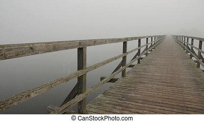 wooden bridge on lake and mist