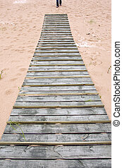 wooden bridge on sand in sea beach