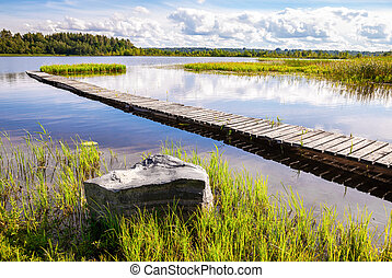 Wooden bridge or a pier on the lake in summer day