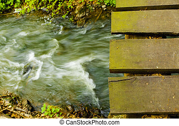 wooden bridge over a mountain stream in the woods