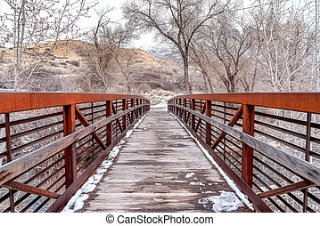 Wooden bridge over creek in the mountain with leafless trees on snowy winter day