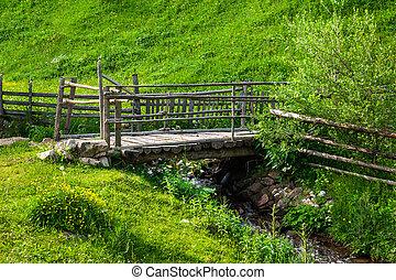 wooden bridge over narrow stream - old wooden bridge of...
