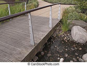 wooden bridge over pebbly pond