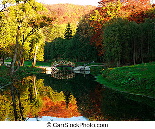 Wooden bridge over river with colorful trees in autumn park