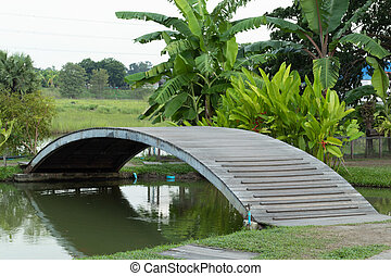 Wooden bridge over the canal in orchard.