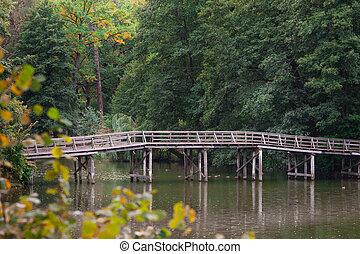 Wooden bridge over the river in summer park