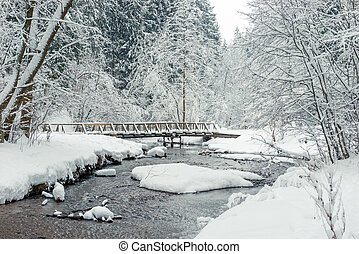 Wooden bridge over the river in the winter snowy forest, beautiful landscape.