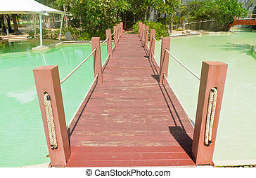 Wooden bridge over the swimming pool.