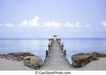 Wooden bridge pier boat in the sea and the bright sky at Koh Kood, Trat in Thailand.