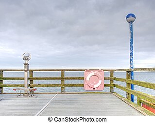 Wooden bridge pier leading to summer sea with blue sky.