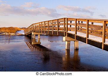 wooden bridge through frozen river at sunrise