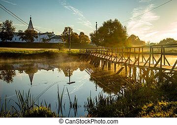 wooden bridge through river in morning sunlight