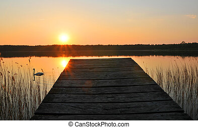Wooden bridge to the lake under the sunset