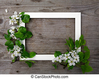 Wooden brown background. White frame with flowers apple. Festive frame. Copy space, flat lay.