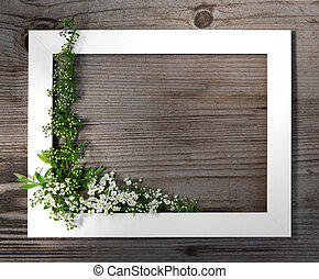 Wooden brown background. White frame with flowers spirea. Festive frame. Copy space, flat lay.
