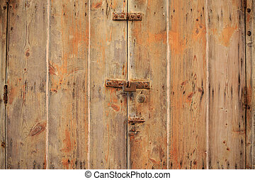 Wooden brown door background locked with rusty padlock. Weathered closed doorway, close up view with details.