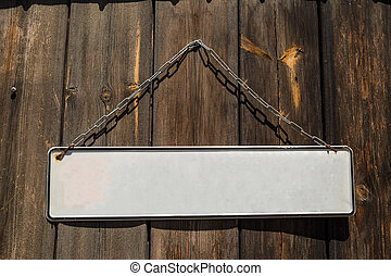 Wooden brown door with a hanging white blank banner label in front of it. Close up view, copyspace.