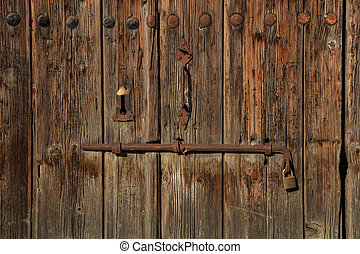 Wooden brown empty timeworn door. Space for text backdrop, rusty latch and padlock. Closeup, details