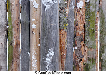 wooden brown fence of rough boards in the snow . Rural life.