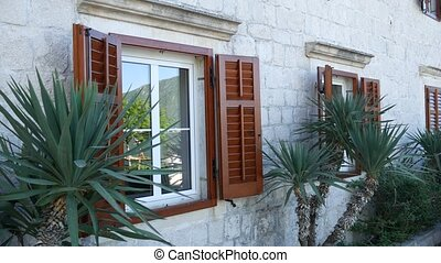 Wooden brown window shutters. The facade of houses in...