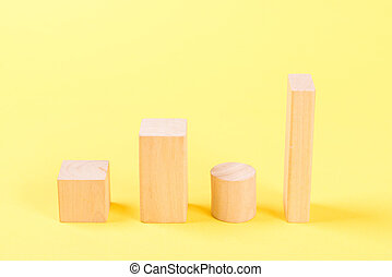 Wooden building blocks on yellow background.