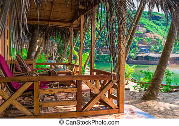 wooden bungalow on the beach in a beautiful location among palm