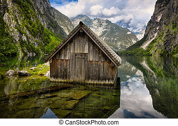 Wooden cabin surrounded by mountains in Lake Obersee