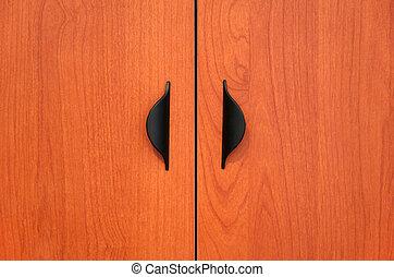 Wooden cabinet doors with black handles.