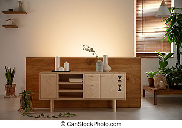 Wooden cabinet with candles and vases surrounded by plants in a natural living room interior. Real photo. Empty wall, place your poster