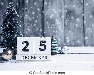 Wooden calendar date and christmas ornament with snow on wood background.