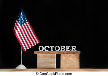 Wooden calendar for October with USA flag on black background. Holidays of the United States of America in October .