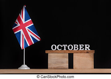 Wooden calendar of October with Great Britain flag on black background. Autumn holidays of UK