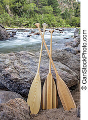 wooden canoe paddles and mountain river - three wooden canoe...