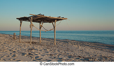 Wooden canopy on the sandy beach at sunset