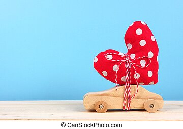 Wooden car with cloth heart against blue