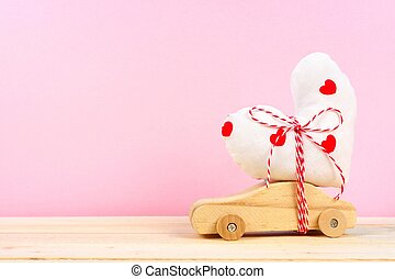 Wooden car with cloth heart against pink