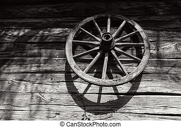 Wooden cart wheel on a wood wall in the rural countryside