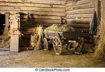 Wooden cart with hay in old barn.