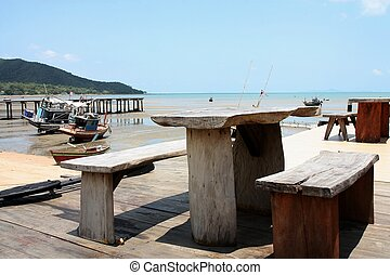 wooden chair and table on the beach