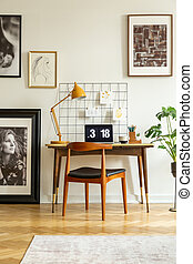Wooden chair at desk with lamp and laptop in white home office interior with posters. Real photo