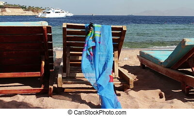 wooden chair at the beach of background of blue sea and white yacht floats