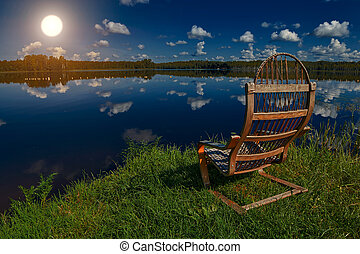 Wooden Chair on a Lake shore at Sunset