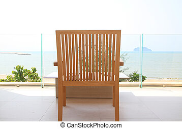 Wooden chair on balcony of the resort with sea and sky