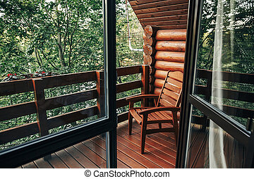 wooden chair on porch of cabin among woods. cottage balcony with view on forest in mountains. atmospheric moment. summer vacation. rural country relax time