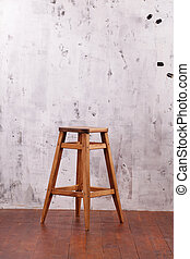 Wooden chair on the background of a concrete wall